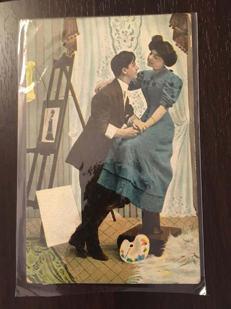 The setting is an artist's studio. A young white man in a suit has his hands around that of a young white woman in a dress. She's sitting on a stool, with her other hand on the man's back.