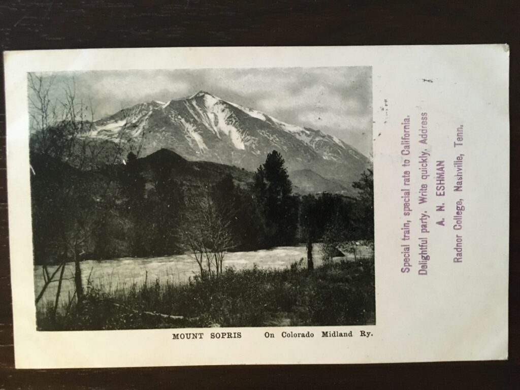 """Photograph of a mountain and river with the caption """"Mount Sopris On Colorado Midland Ry."""" -- on the side is stamped """"Special train, special rate to California. Delightful party. Write quickly. Address A.N. Eshman Radnor College, Nashville Tenn."""""""