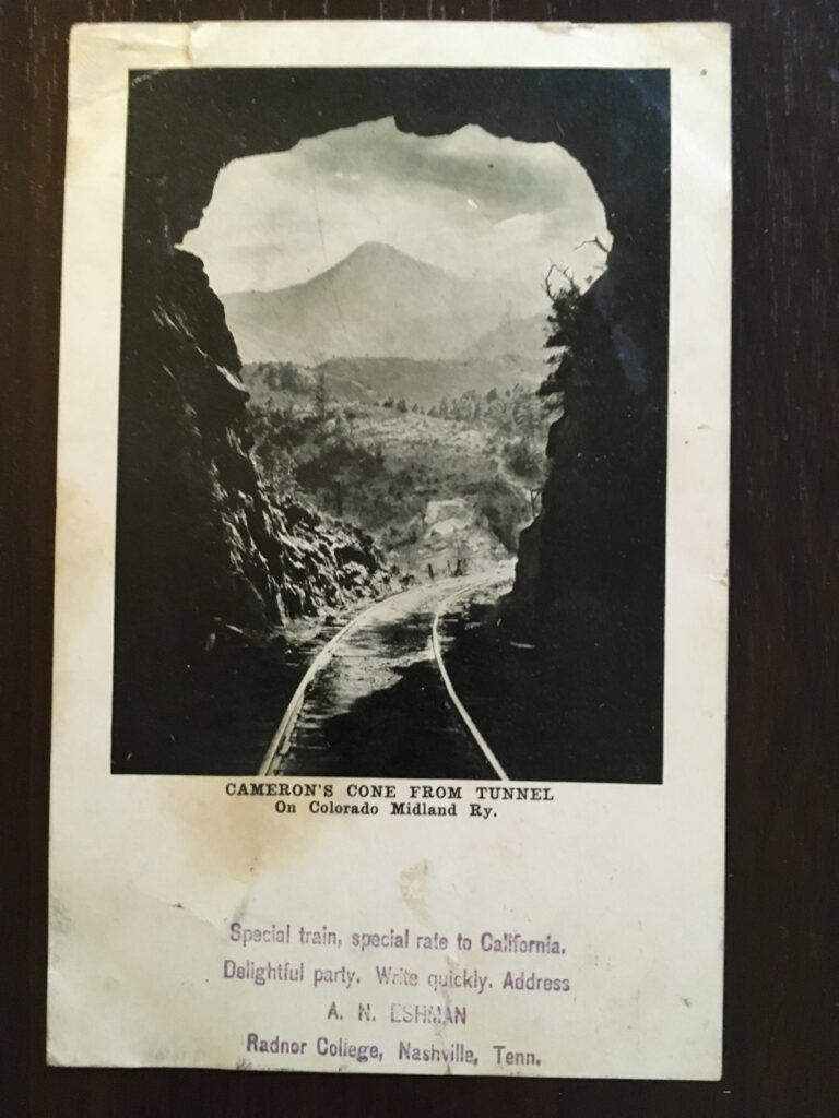 """Photograph of a mountain seen from the end of a railroad tunnel with the caption """"Cameron's Cone From Tunnell On Colorado Midland Ry."""" Below is stamped """"Special train, special rate to California. Delightful party. Write quickly. Address A.N. Eshman Radnor College, Nashville Tenn."""""""