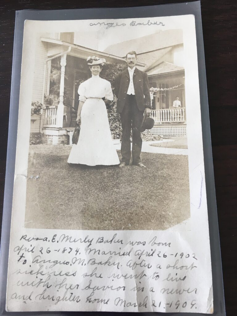 """Image: white woman in a white dress and flower-covered hat and a white man in a full suit, standing on the lawn in front of a large house Manuscript inscription: """"Rosa E. Merly Baker was born April 26-1874. Married April 26-1902 to Angus M. Baker. After a short sickness she went to live with her Savior in a newer and brighter world. March 21-1909."""""""