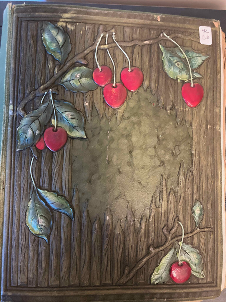 Cover of a postcard album, showing cherries and leaves against a background of wood stakes. The cherries and leaves are raised from the surface of the album.