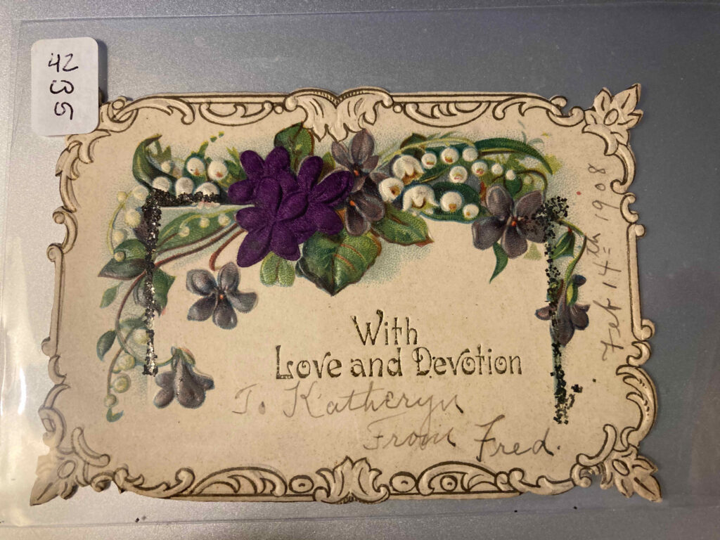 "Front of gift card showing flowers and printed text ""With Love and Devotion"" plus manuscript additions ""To Katheryn From Fred"" and ""Feb 14th 1908"""