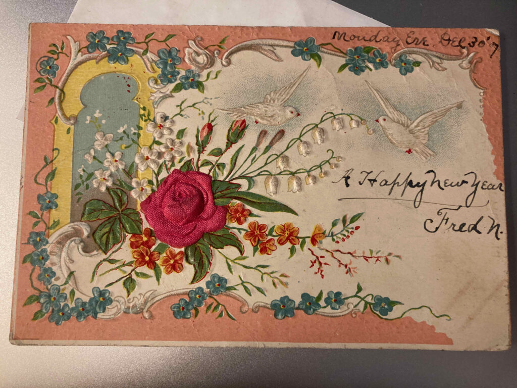 """A red rose, other flowers, and two doves. Manuscript additions: """"Monday Eve Dec. 30'7"""" and """"A Happy New Year Fred N."""""""