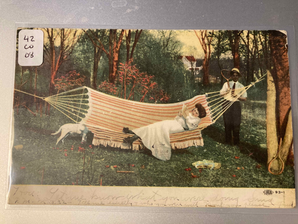 """A white woman lies in a hammock reading a letter, as a white man carrying a tennis racket heads toward her. Message below: """"Let me know what you were doing Sund P.M. Mar 22—Tell me exactly  + who you were with Wont you please Fred"""""""