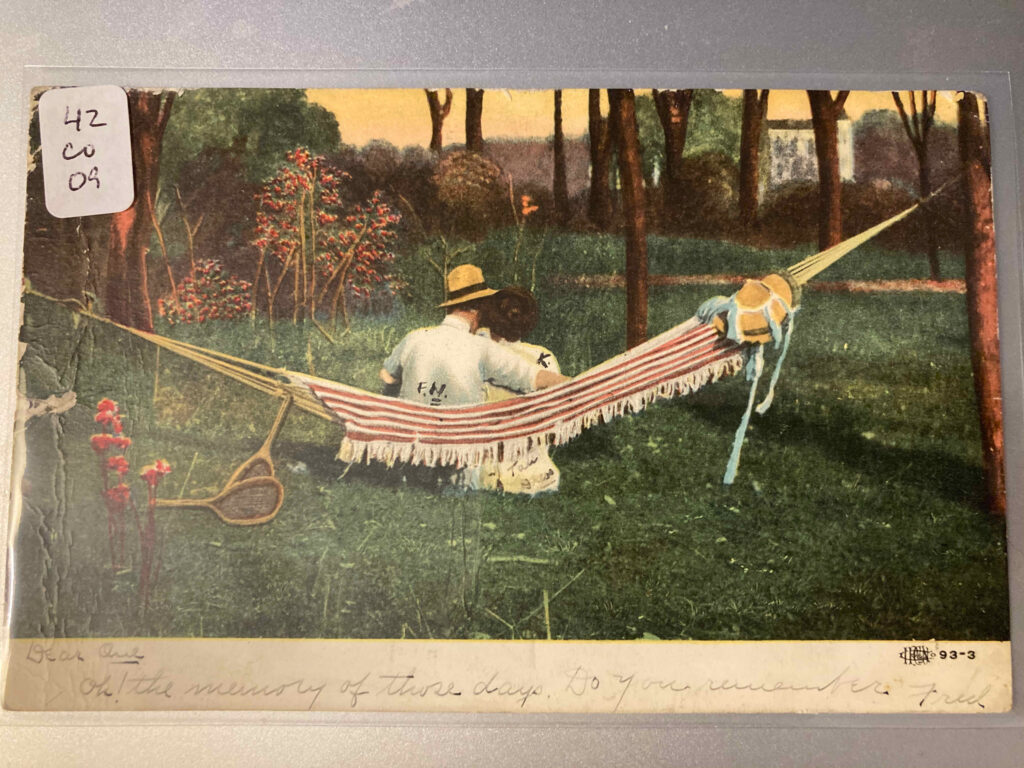 """White man and woman sitting in a hammock. Message inscribed below: """"Dear Girl Oh! The memory of those days. Do you remember Fred"""""""