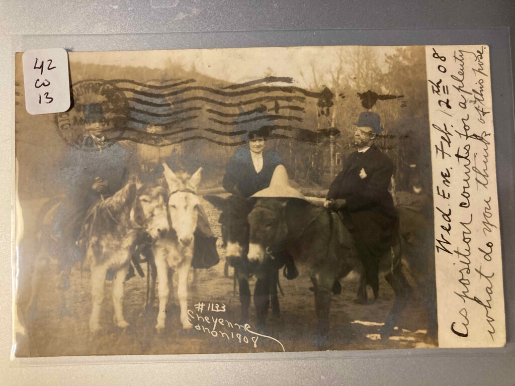 "Two white men and two white women on burros or donkeys. Printed text ""#1133 Cheyenne Canon 1908"" Manuscript addition ""Wed Eve Feb. 12th 08 As position counts for a plenty what do you think of this pose?"""
