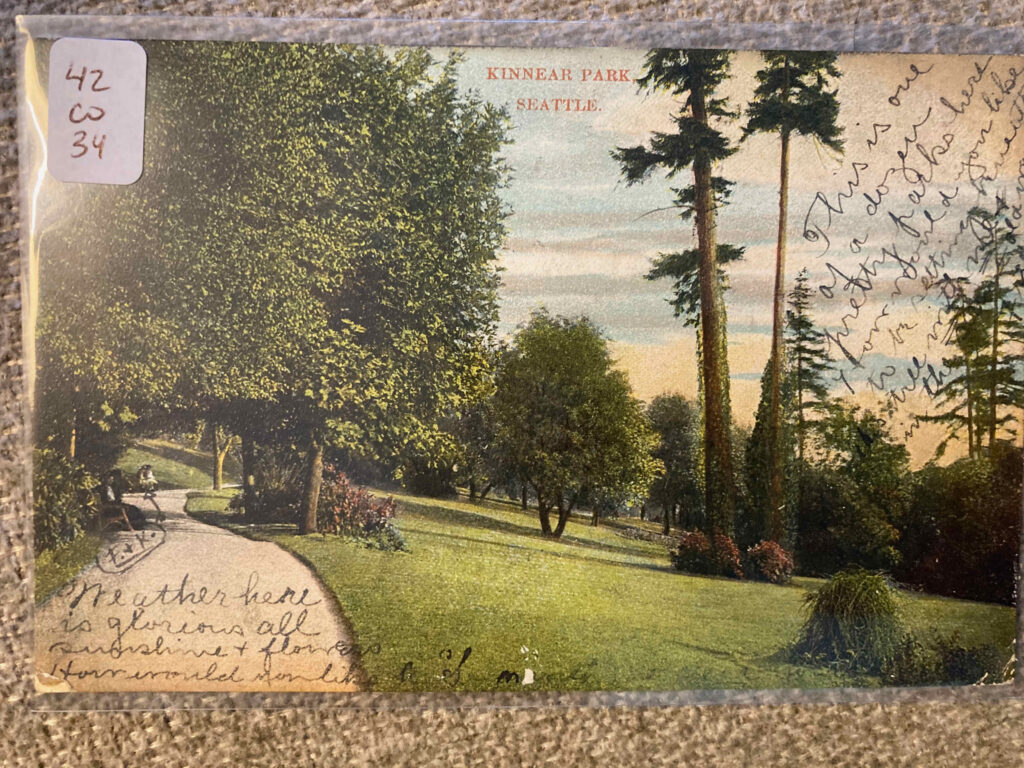 "Park view with path, trees, and grassy swaths. Manuscript additions: ""F+K""; ""Weather here is glorious all sunshine + flowers How would you like to [several words illegible]"", and ""This is one of a dozen pretty parks here How would you like to be sitting beneath the tree with me + in the [unclear] old way."""