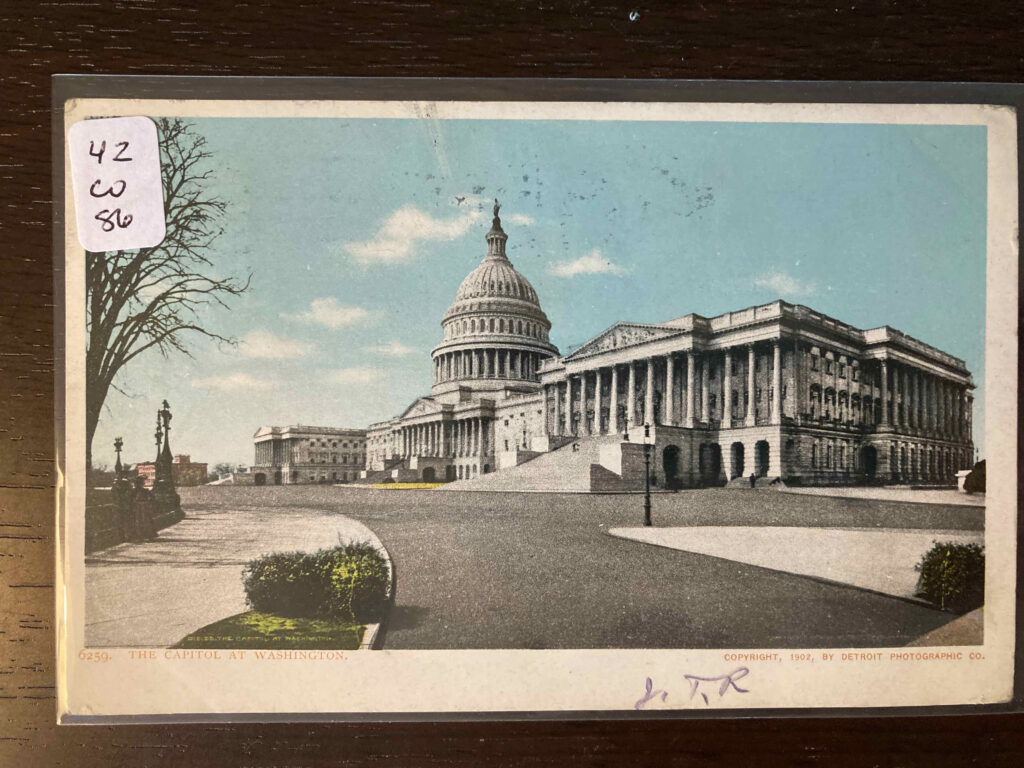 Colorized photo of the Capitol at Washington, D.C. Handwritten initials at bottom center-right.