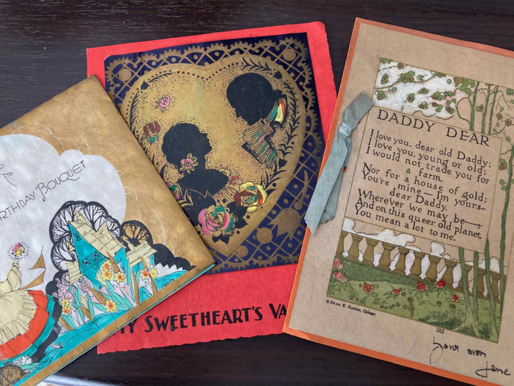 """A birthday card on the left, valentine in the center, and card addressed to """"Daddy Dear"""" on the right."""
