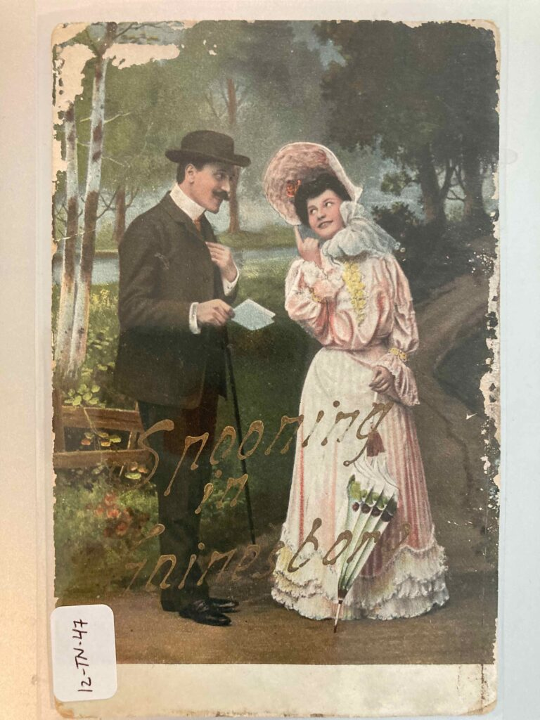 """A man and a woman in a park setting. He's holding a letter or card. She's pointing a finger. Caption """"Spooning in Gainesboro."""""""