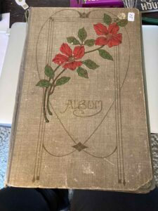 Postcard album with a spray of flowers across the front