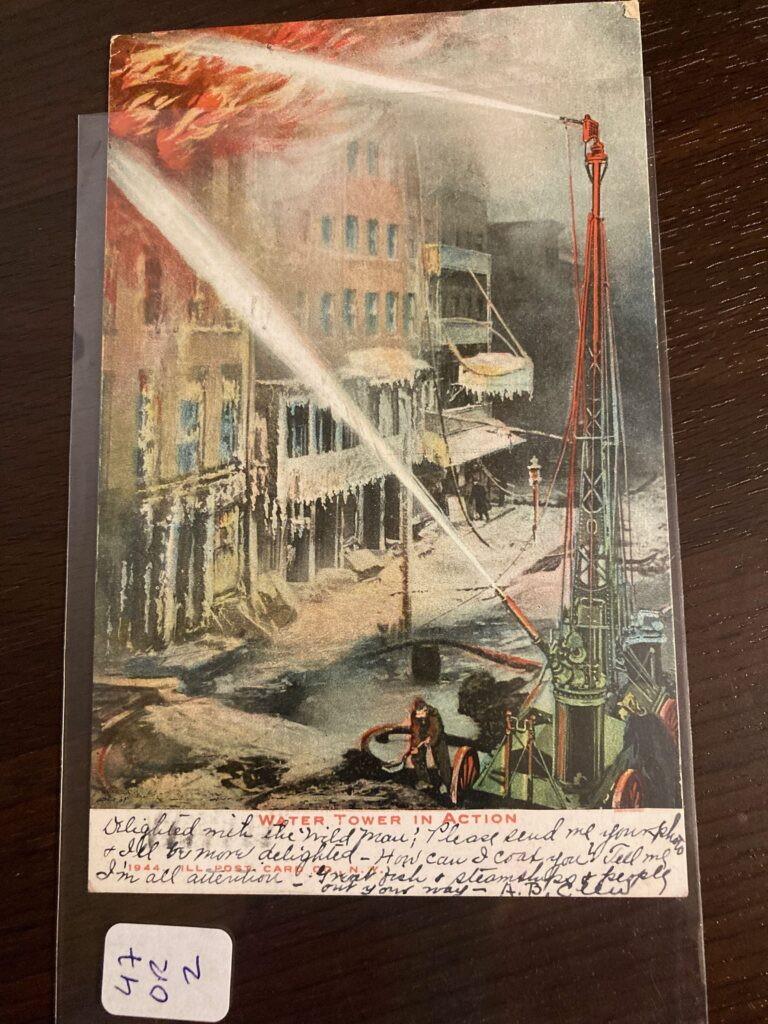 """Image of a water tower blasting water on a burning building. Titled """"Water Tower in Action,"""" Image #1944 from the Ill. Post Card Co., N.Y."""